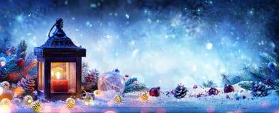 Snöig lykta med granfilialer och struntsaker arkivbilder