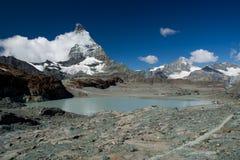 Snöig Matterhorn med moln och glaciärsjön Arkivfoto