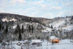 Snöig by på bergen Arkivfoto