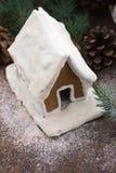 Snöig pepparkakahus med snöflingajulträdet och jordklot på bakgrund för stenvägg Hemlagade julkakor - gingerbrea arkivfoto