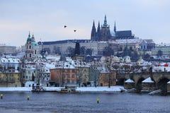 Snöig Prague för afton gotisk slott med Charles Bridge, Tjeckien Royaltyfri Fotografi