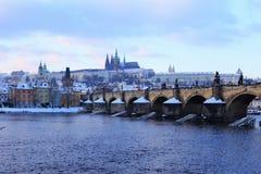 Snöig Prague för afton gotisk slott med Charles Bridge, Tjeckien Royaltyfria Bilder