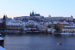 Snöig Prague för afton gotisk slott med Charles Bridge, Tjeckien Arkivfoto