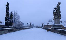 Snöig Prague för morgon gammal stad med brotornet och St Francis av den Assisi domkyrkan från Charles Bridge med dess barocka sta Arkivfoton