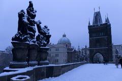 Snöig Prague för morgon gammal stad med brotornet och St Francis av den Assisi domkyrkan från Charles Bridge med dess barocka sta Fotografering för Bildbyråer