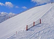 Snöig skidar lutningen i bergen Arkivfoto