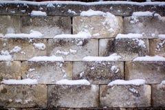 Snöig stena väggen på en kall vinterdag royaltyfria bilder