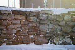 Snöig stenvägg i solen Arkivfoton