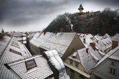 Snöig tak i österrikisk stad av Graz med gränsmärkeclocktower Arkivfoton