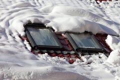 Snöig tak med fönster Arkivbild