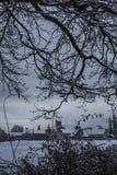 Snöig by till och med träd Royaltyfri Fotografi