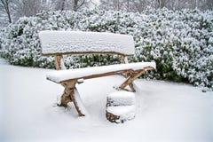 Snöig träbänk i skogen Royaltyfria Foton