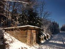 Snöig träkabin Arkivbild