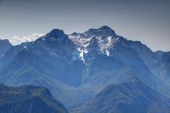 Snöig Triglav med den forested Vrata och Kot dalen i Julian Alps royaltyfri bild