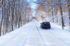 Snöig väg i vinterskog med singelbilen Arkivfoton