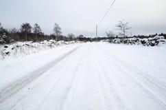 Snöig väg som omges av stenväggar Arkivfoto