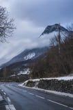 Snöig väg till och med berg Royaltyfria Foton