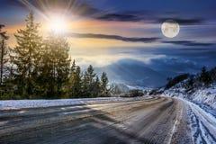 Snöig väg till och med prydlig skog i berg royaltyfria bilder