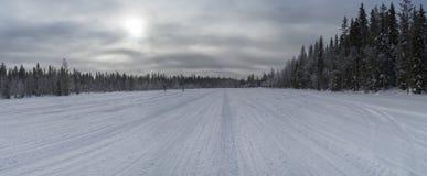 Snöig väg till och med skog med snövesslaspår i en ljus vinterdag Arkivfoton