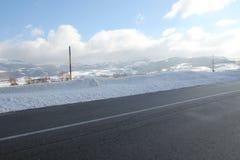 Snöig väg under strålar för en blå himmel och sols Royaltyfri Foto