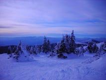 Snöig vinterlandskap i bergen på skymning