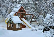 Snöig vinterträdgårdlekplats Arkivfoto