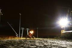 Snökanonen i skidasemesterorten på natten börjar att snöa ner skidalutningen Royaltyfri Foto