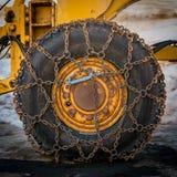 Snökedjor på det stora gummihjulet Arkivbild