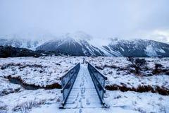 Snölandskap med fotmoment över bron i Nya Zeeland arkivfoto