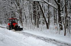Snömaskinen, den röda traktoren gör ren snön från det insnöat bakgrunden av skogen royaltyfri bild