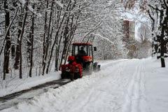 Snömaskinen, den röda traktoren gör ren snön från det insnöat bakgrunden av skogen arkivbilder