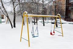 Snön ligger på gungan för barn` s arkivbild