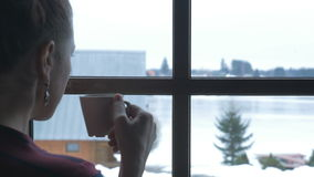 Snön utanför fönstret och det varma teet Ung kvinna med koppen av den varma drinken som står på fönstret Bak ett fönster a arkivfilmer