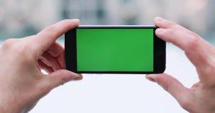 Snönedgångar över smartphone för hand för man` s en hållande med den gröna skärmen i hans arm och knackar lätt på något på den lager videofilmer