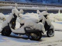 Snöparen - gatabildspråk - två sparkcyklar som täckas i snö Royaltyfri Bild