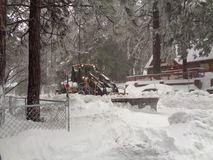 Snöplog som gör klar den bostads- gatan i körande vårar, San Bernardino Mountains CA fotografering för bildbyråer