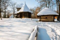 Snöräkning i en rumänsk by med en gammal träkyrka Royaltyfria Foton