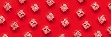 Snör åt den röda gåvaasken för modellen med dekorativt på röd bakgrund som lägenheten för den bästa sikten lägger Semestra pres f royaltyfria bilder