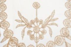 Snör åt försiktig beiga för närbilden med utsmyckat blom- motiv på vitbaksida arkivfoton