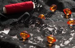 Snör åt orange pärlor för exponeringsglas och den röda rullen av tråden på den svarta prydnaden på vit arkivfoton