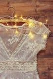 Snör åt vit virkning för tappning överkanten på hängare med girlandljus på träbakgrund Royaltyfri Fotografi