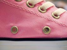 Snörde åt rosa moderiktiga gymnastikskor med skyddshylsor, slut upp arkivfoton