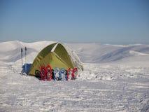 Snöskor och tält på insnöat bergen royaltyfri bild