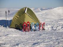 Snöskor och tält på insnöat bergen royaltyfria foton