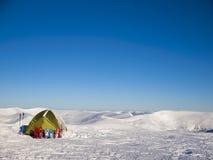 Snöskor och tält på insnöat bergen royaltyfri fotografi