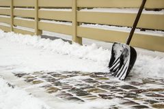 Snöskyffel nära staketet på en snöig väg royaltyfri fotografi