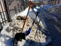 Snöskyffel- och isyxa i snön mot bakgrunden av en tegelplatta och ett staket i vår eller vinter royaltyfri foto