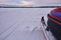 Snövessla skidar och den fryste sjön Arkivbild