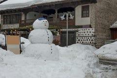 Snövinterfyrkant i den Bansko staden med forntida hus, vinrankan och snö-mannen arkivfoton