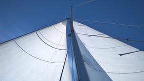 Snövitt seglar mot en ren ljus blå himmel på en solig sommardag royaltyfria bilder